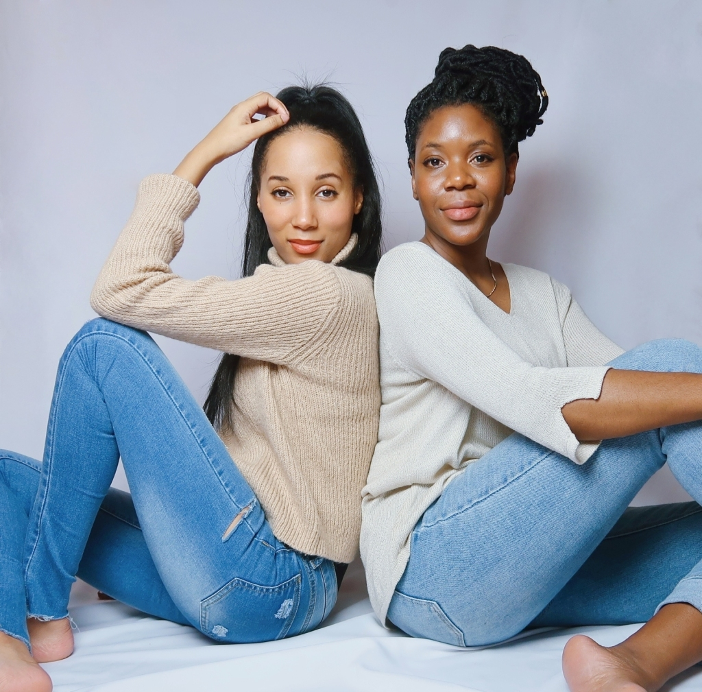 two women waving jeans and sweater sitting